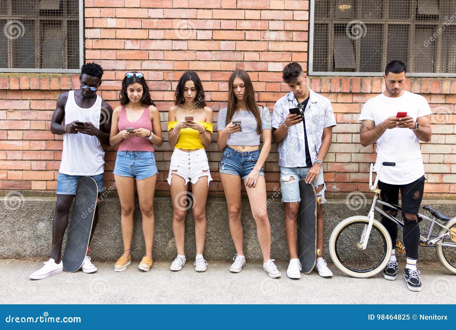 Groupe de jeunes amis de hippie à l aide du téléphone intelligent dans une zone urbaine