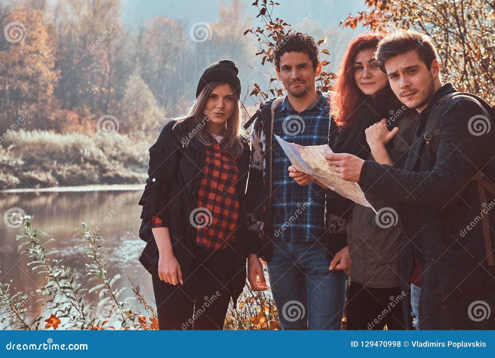 Groupe de jeunes amis trimardant dans la forêt colorée d automne, regardant la carte et prévoyant la hausse