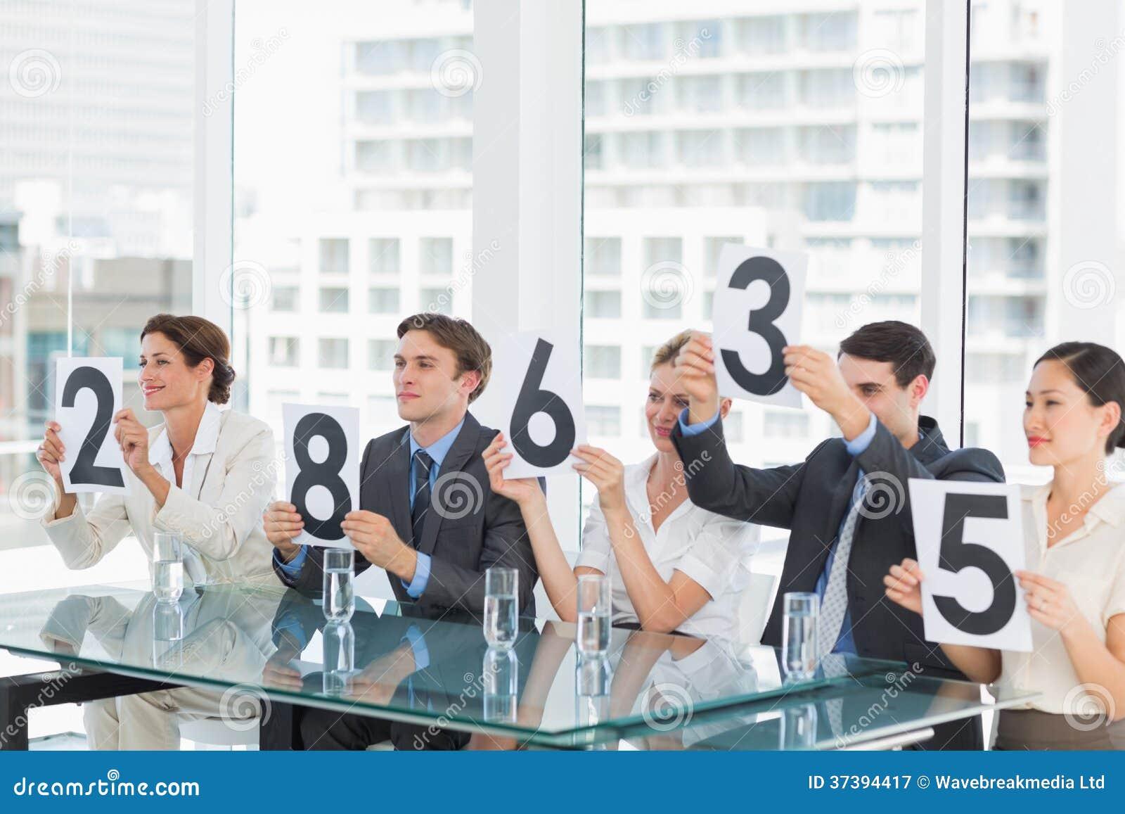 Groupe de juges de panneau tenant des signes de score