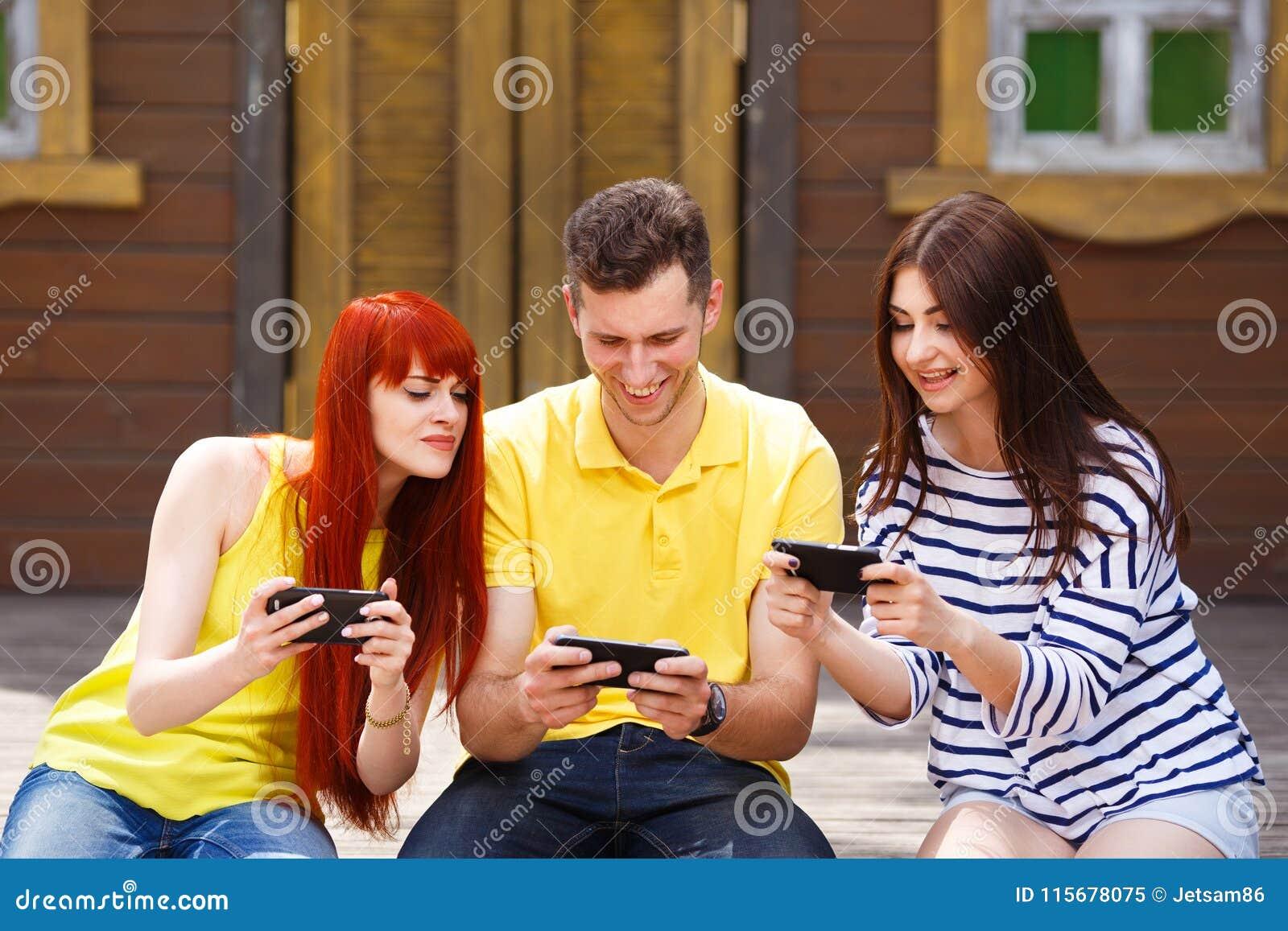 Groupe de la jeunesse riant jouant le jeu vidéo mobile dehors