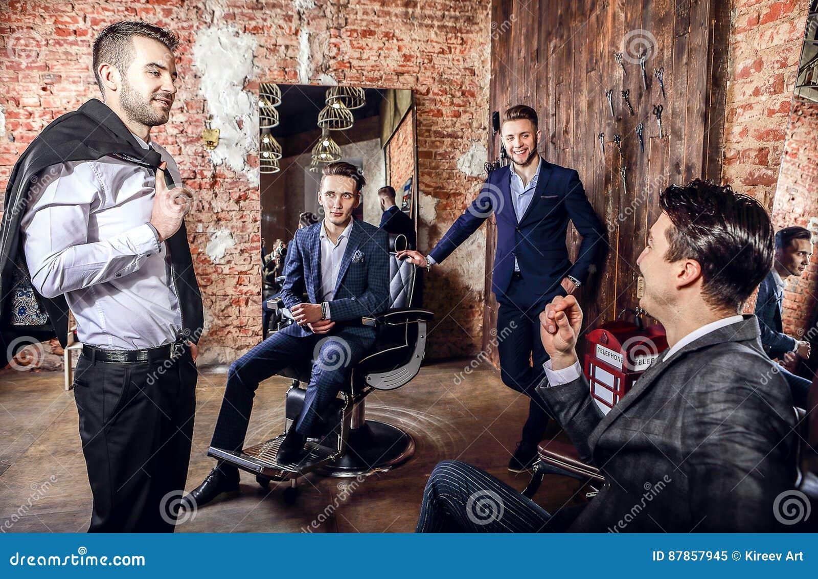 Groupe de la pose des jeunes hommes positifs élégants dans l intérieur du raseur-coiffeur