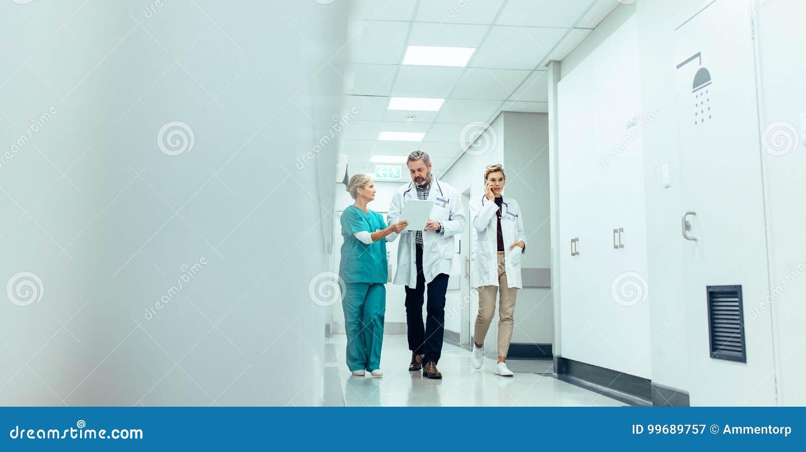 Groupe de médecins avec le presse-papiers marchant le long du couloir d hôpital