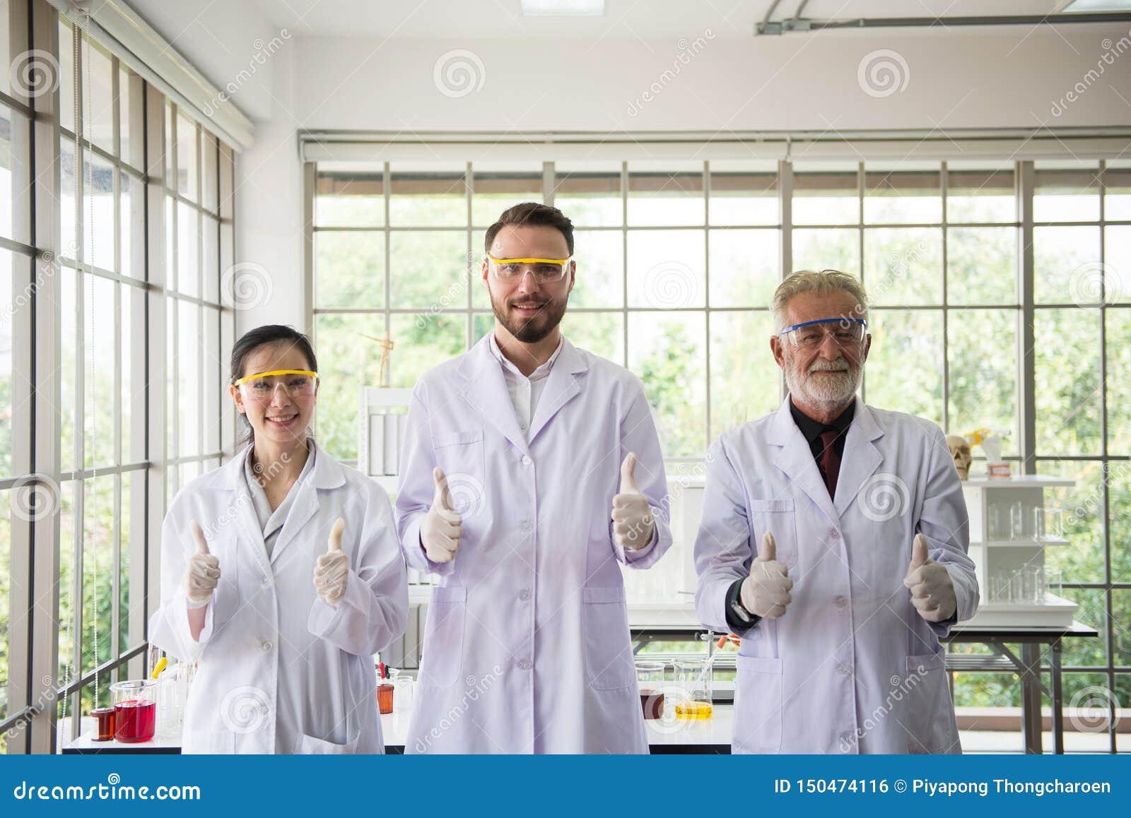 Groupe de personnes de scientifiques tenant et montrant le pouce ensemble dans le laboratoire, le travail d équipe réussi et le f