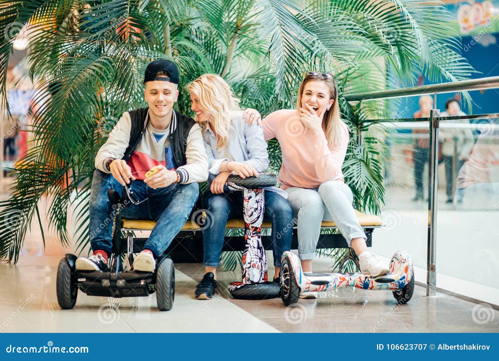 Groupe de personnes sur le hoverboard électrique de scooter se reposant au banc et à l aide du téléphone