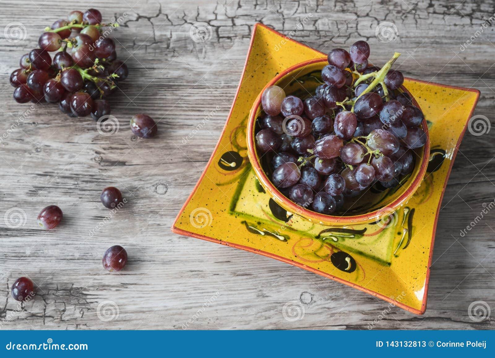 Groupe de raisins rouges dans la cuvette orange, sur le fond en bois
