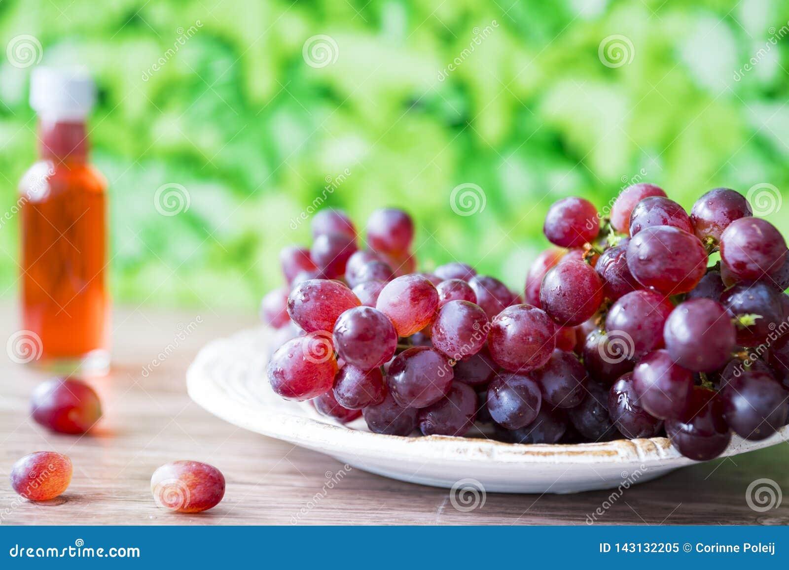 Groupe de raisins rouges du plat blanc, sur le fond vert de feuilles L espace pour le texte