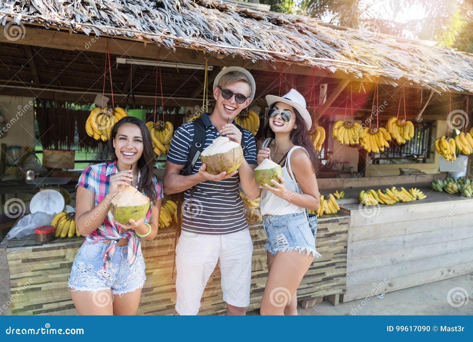 Groupe de touristes buvant la noix de coco sur le marché en plein air de la Thaïlande, l homme gai et les femmes dans le bazar tr