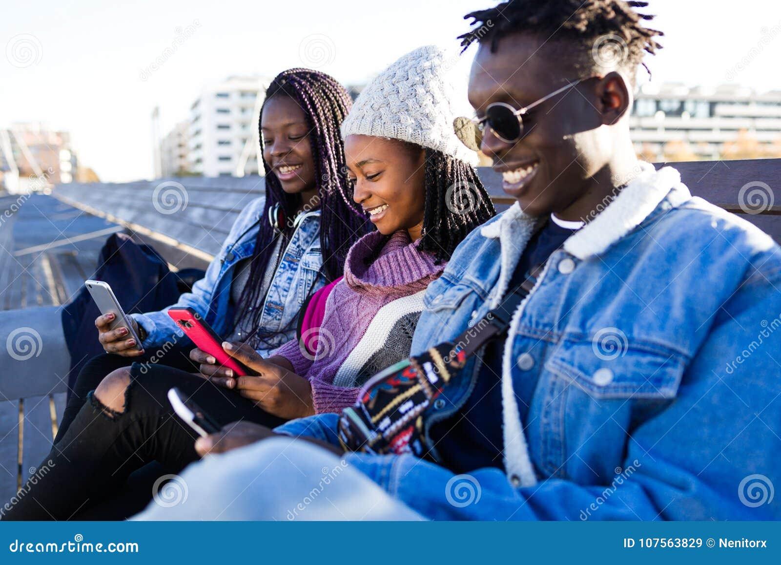 Groupe de trois amis à l aide du téléphone portable dans la rue
