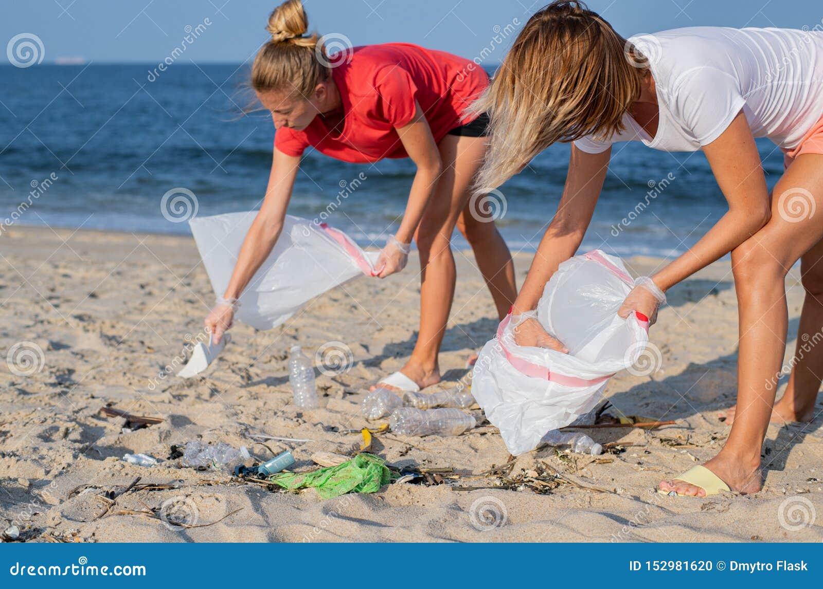 Groupe de volontaires nettoyant la ligne de plage Les gens rangeant des déchets sur le bord de mer Concept d ?cologie