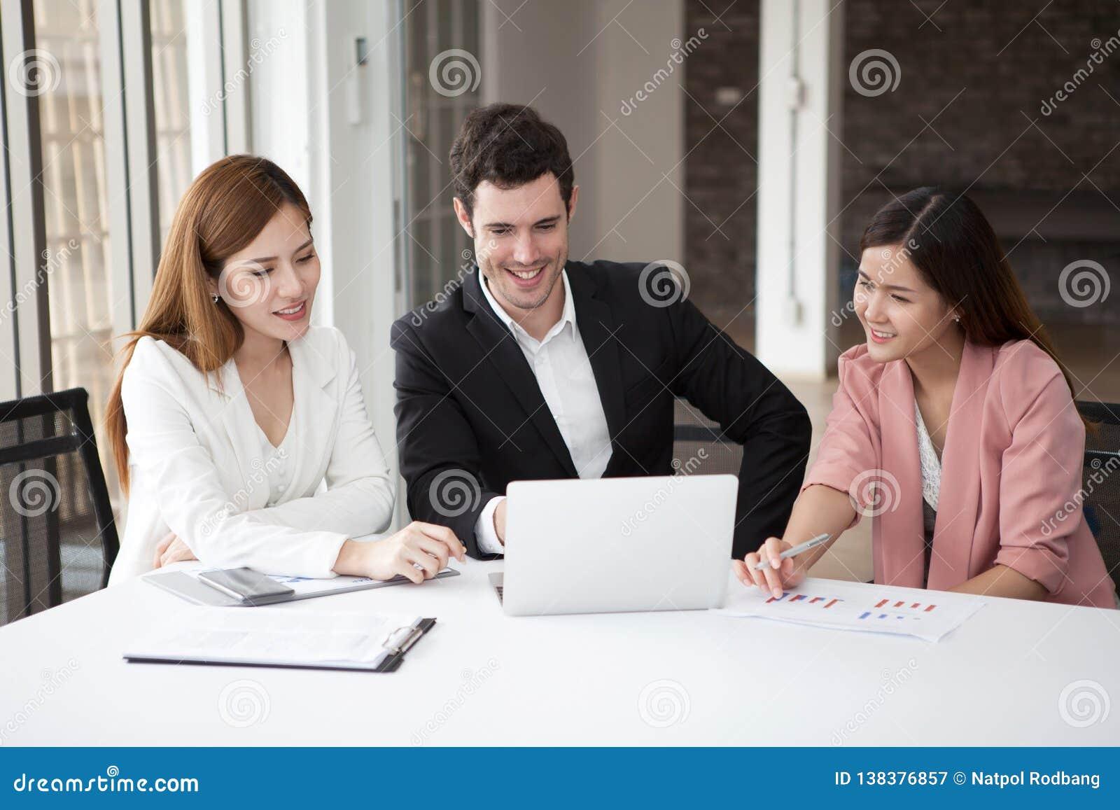 Groupe des hommes heureux et de la femme d hommes d affaires travaillant ensemble sur l ordinateur portable dans le lieu de réuni
