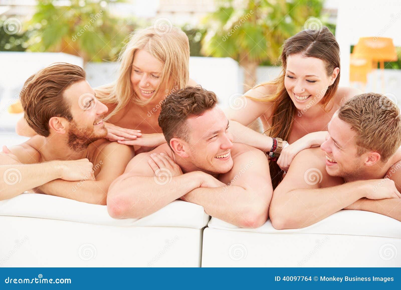 Groupe des jeunes en vacances détendant par la piscine