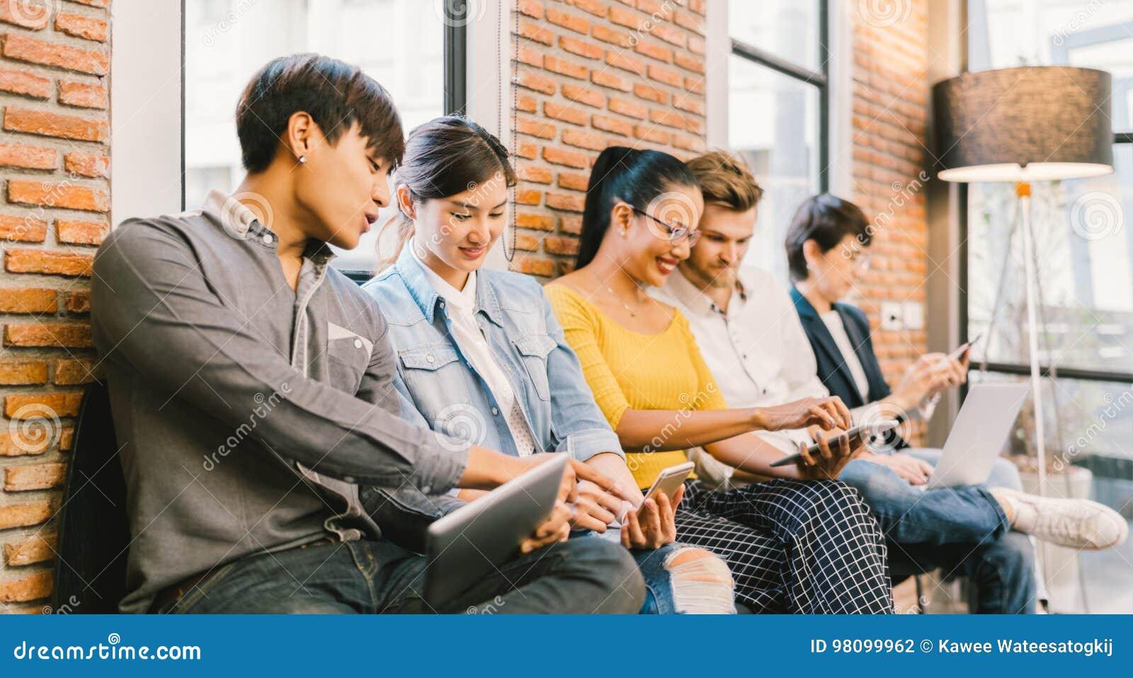 Groupe divers multi-ethnique de jeunes et adultes à l aide du smartphone, ordinateur portable, comprimé numérique ensemble