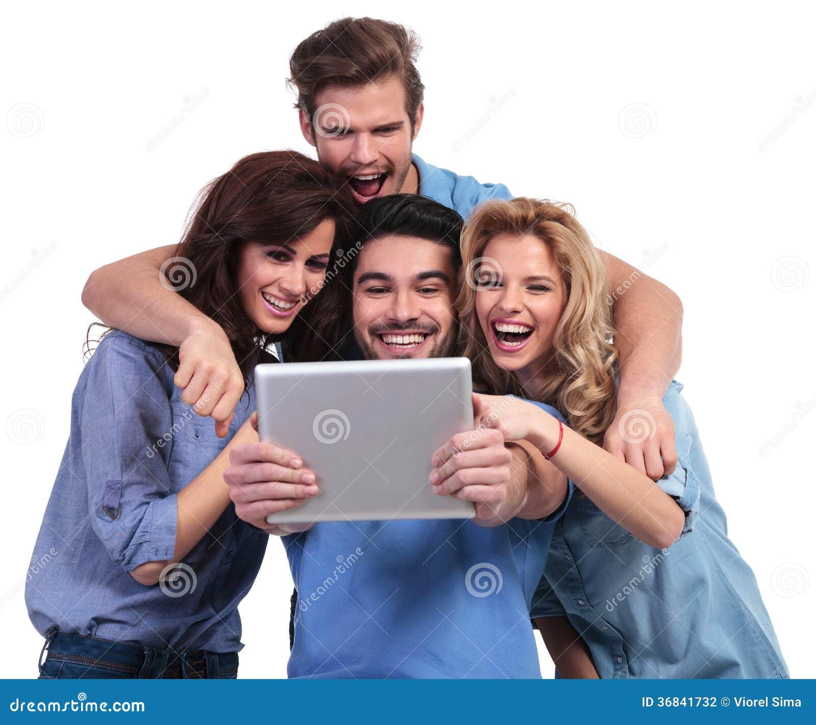 Groupe enthousiaste d amis lisant la substance étonnante sur leur table
