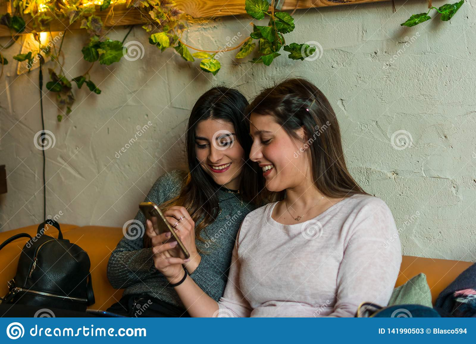 Groupe heureux d amis regardant un mobile le restaurant de barre de brasserie