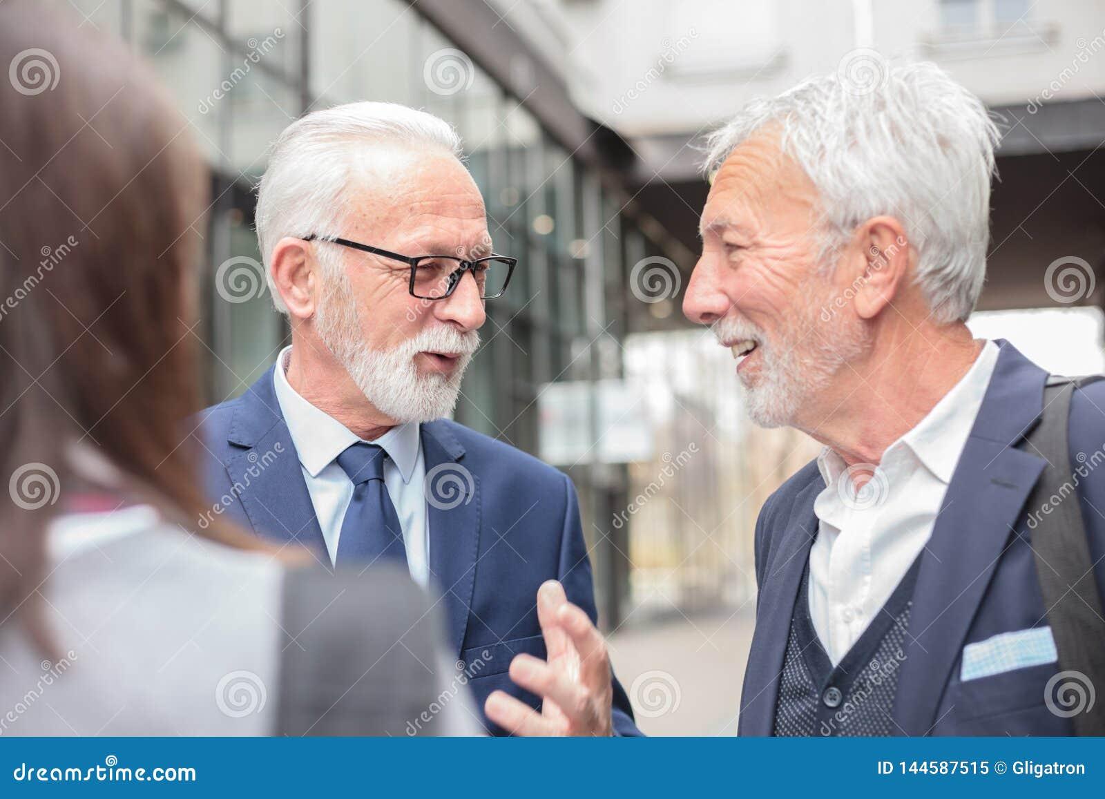 Groupe mixte d hommes d affaires se réunissant et discutant devant un immeuble de bureaux