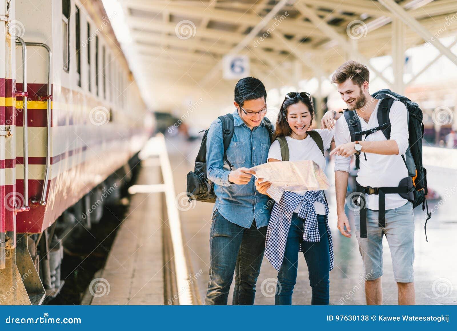 Groupe multi-ethnique d amis, de voyageurs de sac à dos, ou d étudiants universitaires employant la navigation locale de carte en