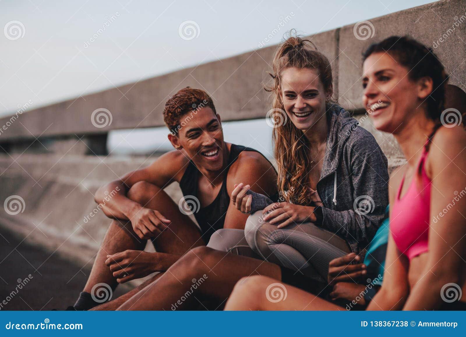 Groupe multi-ethnique de personnes de forme physique se reposant après séance d entraînement