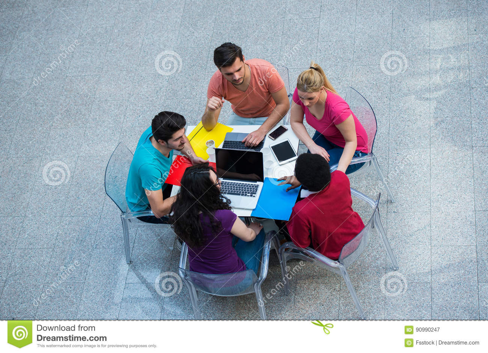 Groupe multiracial de jeunes étudiants étudiant ensemble Coup courbe des jeunes s asseyant à la table