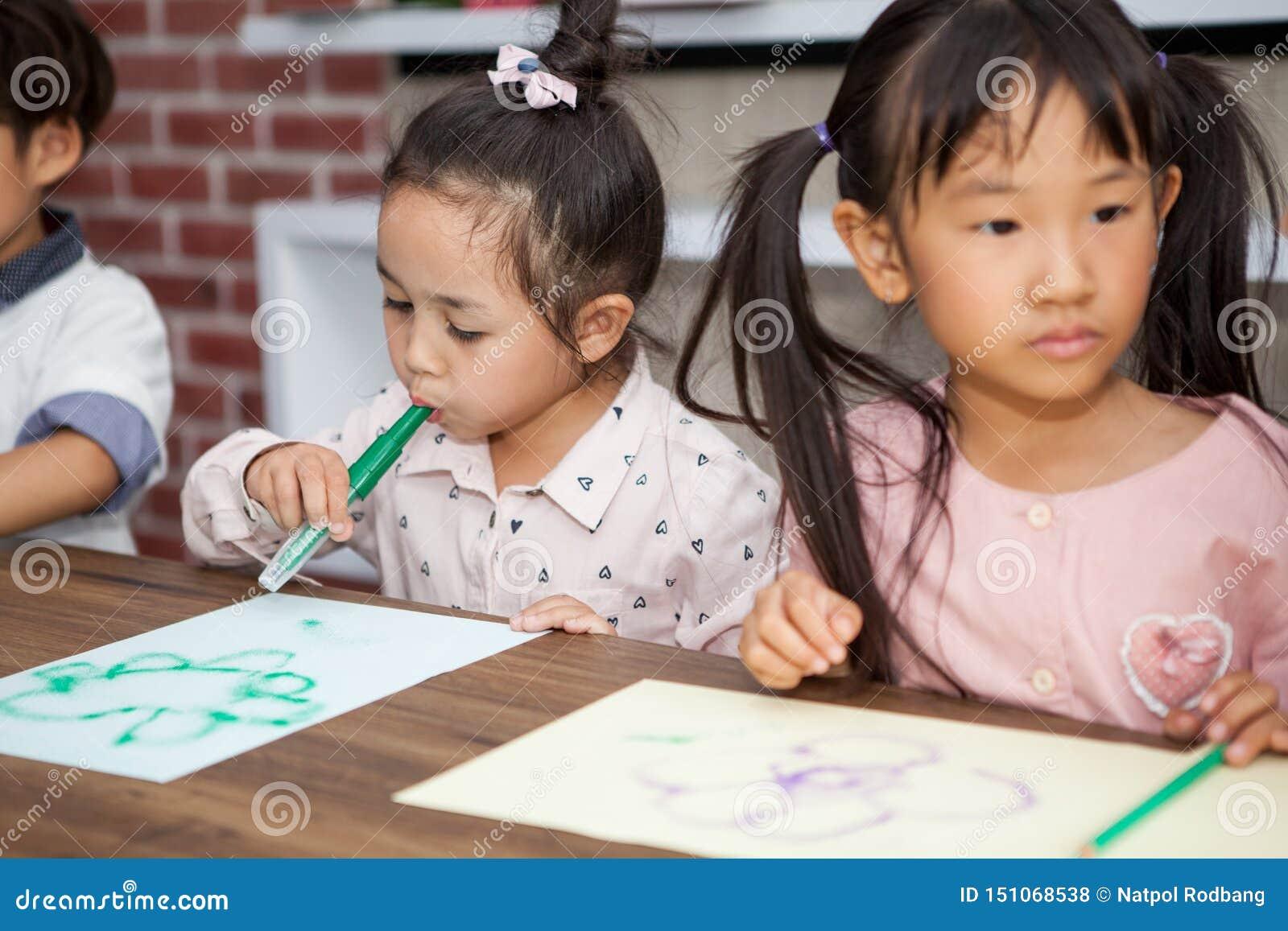 Groupe petite de la peinture de soufflement mignonne de stylo de couleur d étudiante de fille et de garçon ainsi que le professeu