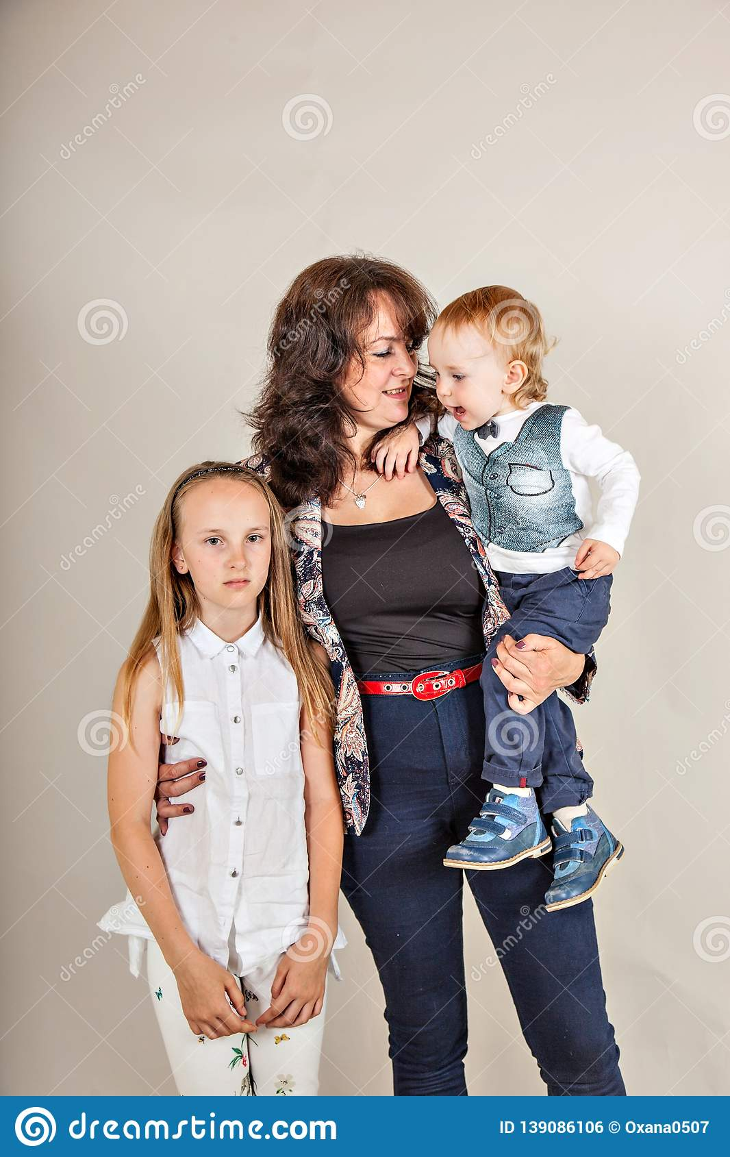 Growth portrait of happy mother with two children isolated gray background.