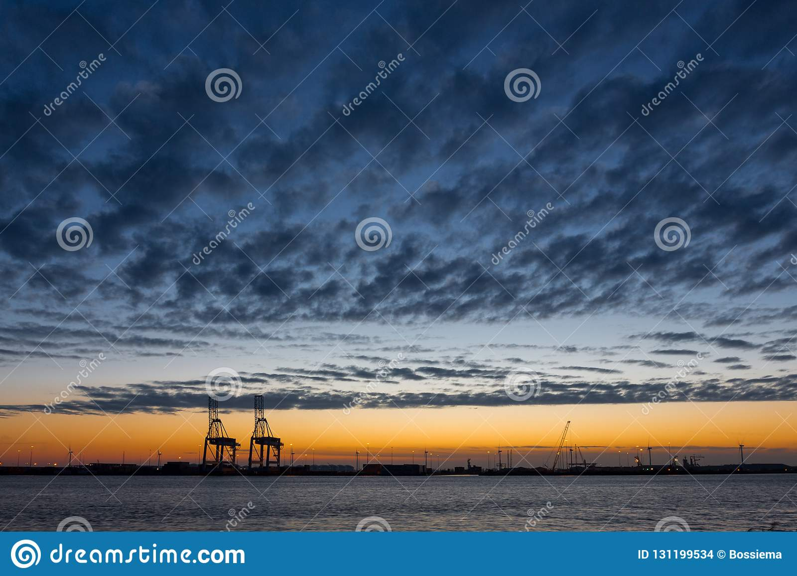 Gru industriali in un porto al tramonto