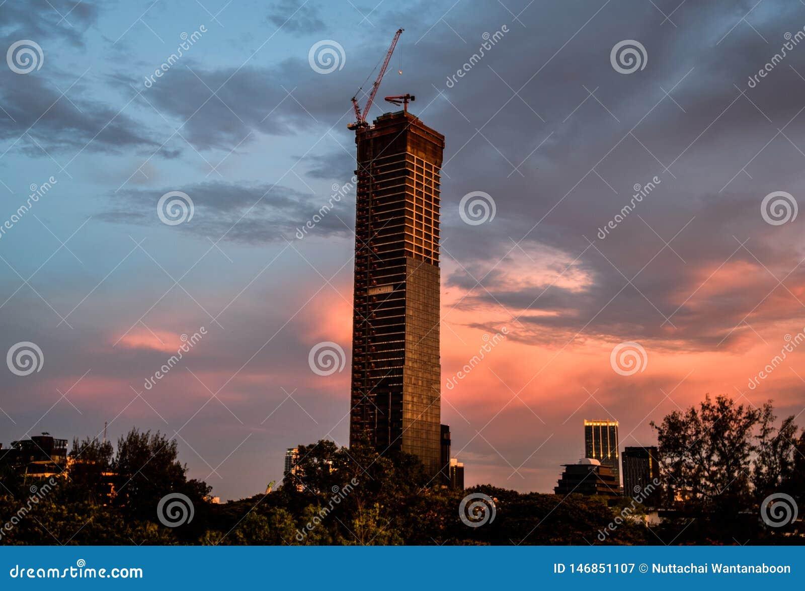 Gru a torre sopra una costruzione non finita nella sera a Bangkok, Tailandia