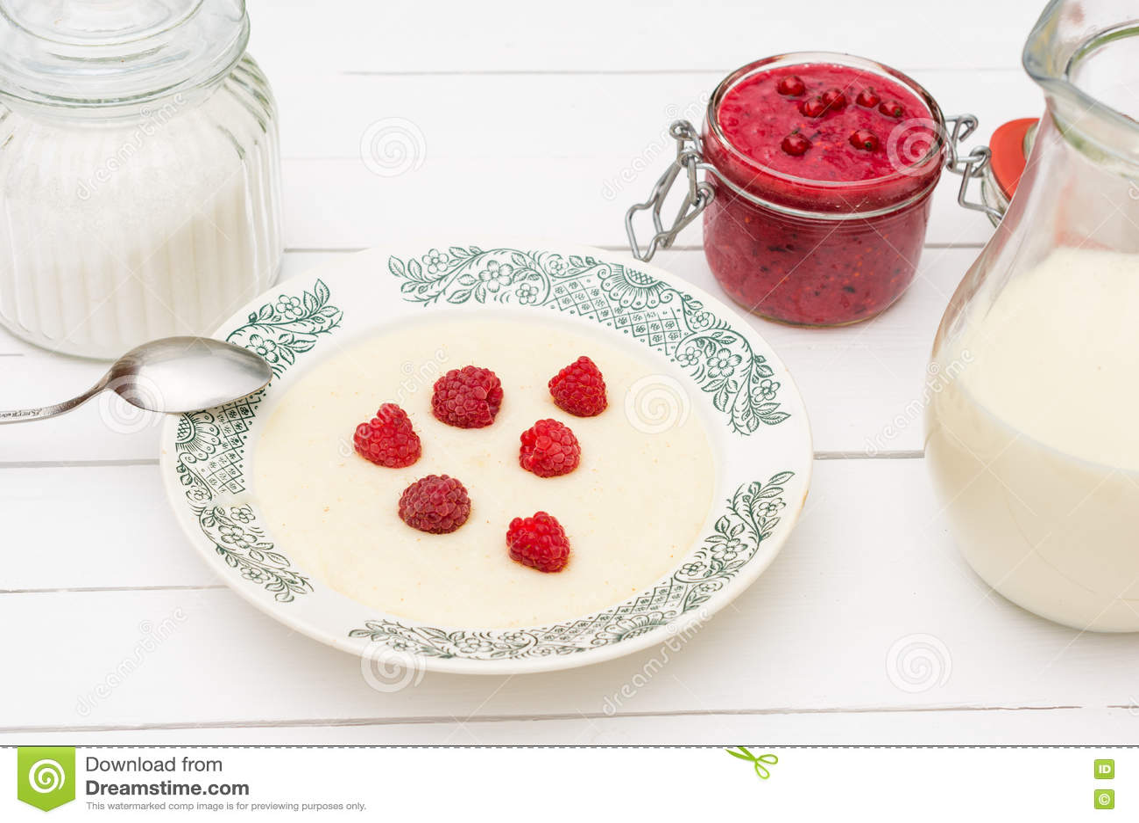 Gruau de semoule avec les framboises, le pot avec du lait et la confiture pour le petit déjeuner