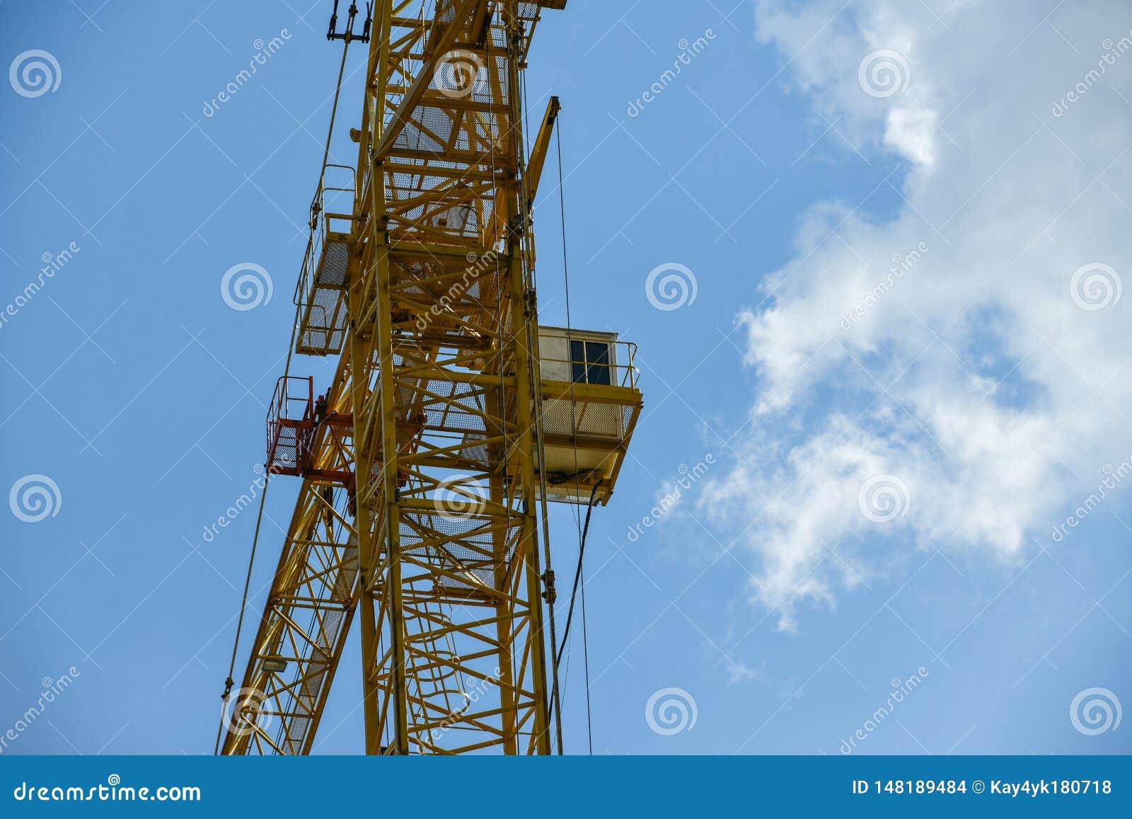 Grue de construction ayant beaucoup d étages avec une longue flèche de couleur jaune contre le ciel bleu au-dessus d un nouveau b