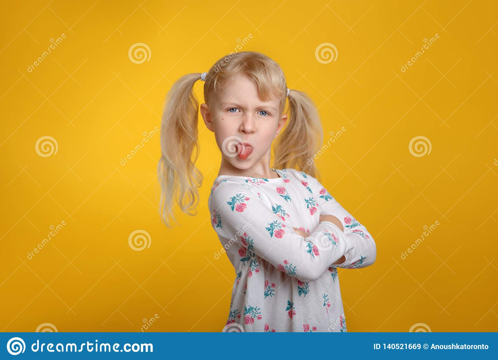 Grumpy angry Caucasian blonde girl with blue eyes in white dress posing in studio on yellow background