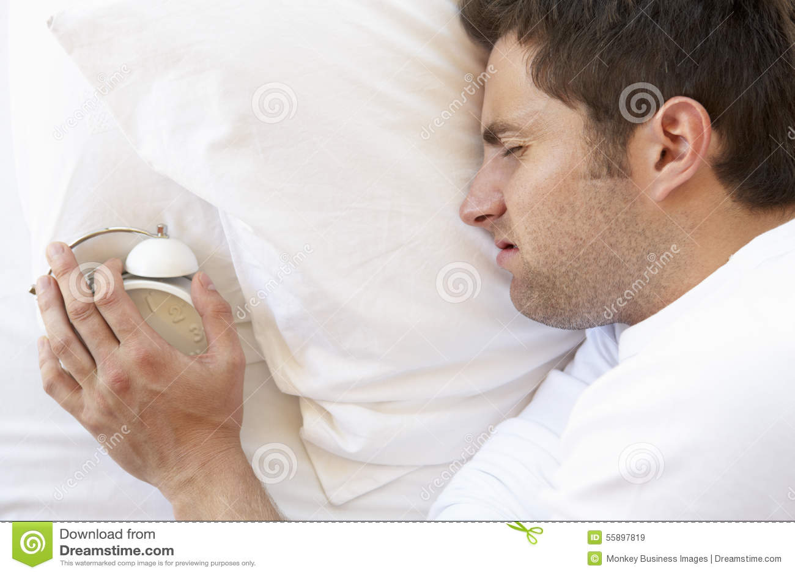 Grumpy Man In Bed Turning Off Alarm Clock Stock Image