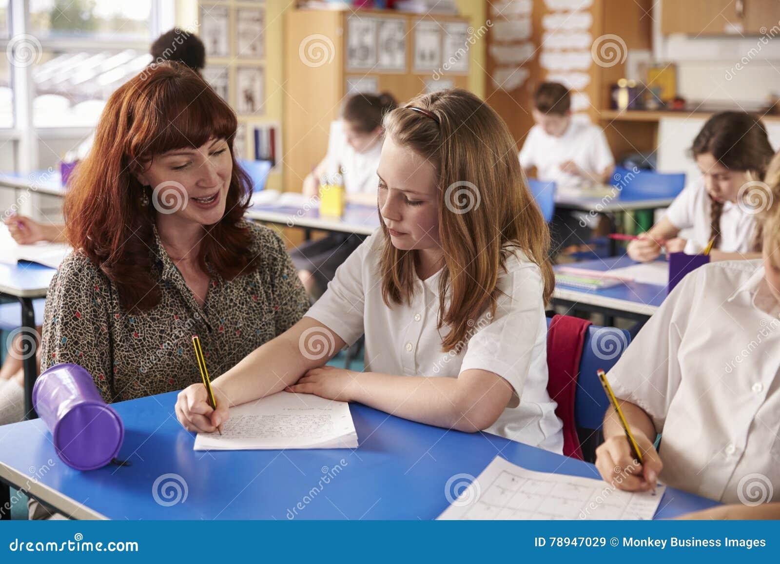 Grundschullehrer, der einem Mädchenschreiben an ihrem Schreibtisch hilft