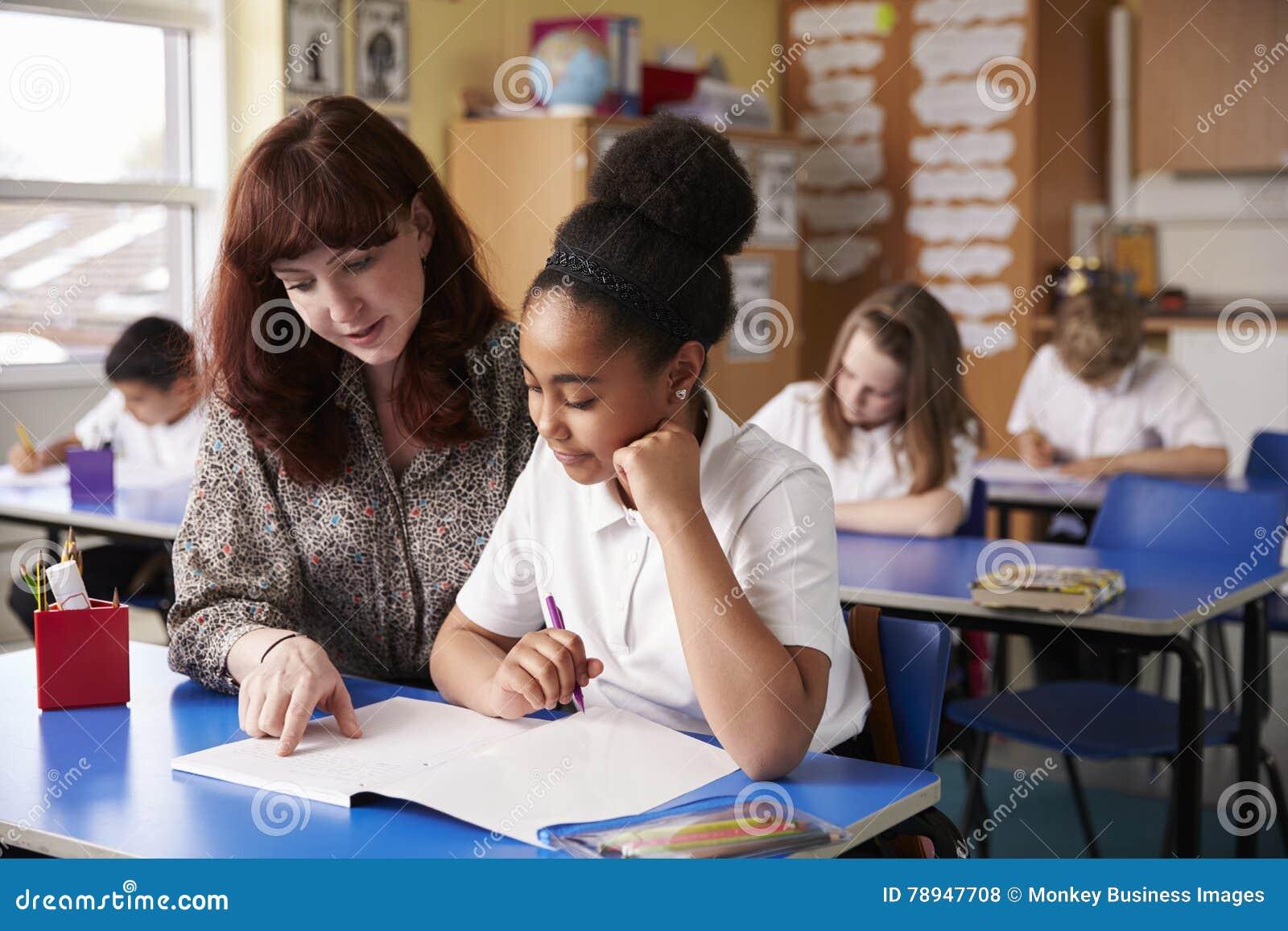 Grundskola för barn mellan 5 och 11 årlärare som hjälper en skolflicka på hennes skrivbord