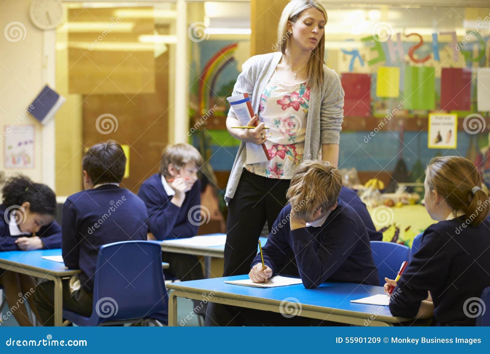 Grundskolaelever som sitter undersökning i klassrum