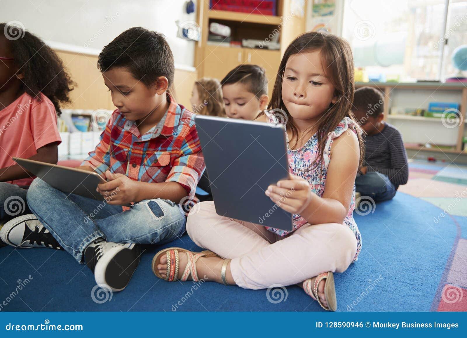 Grundskolagrupp som använder upp minnestavladatorer, slut