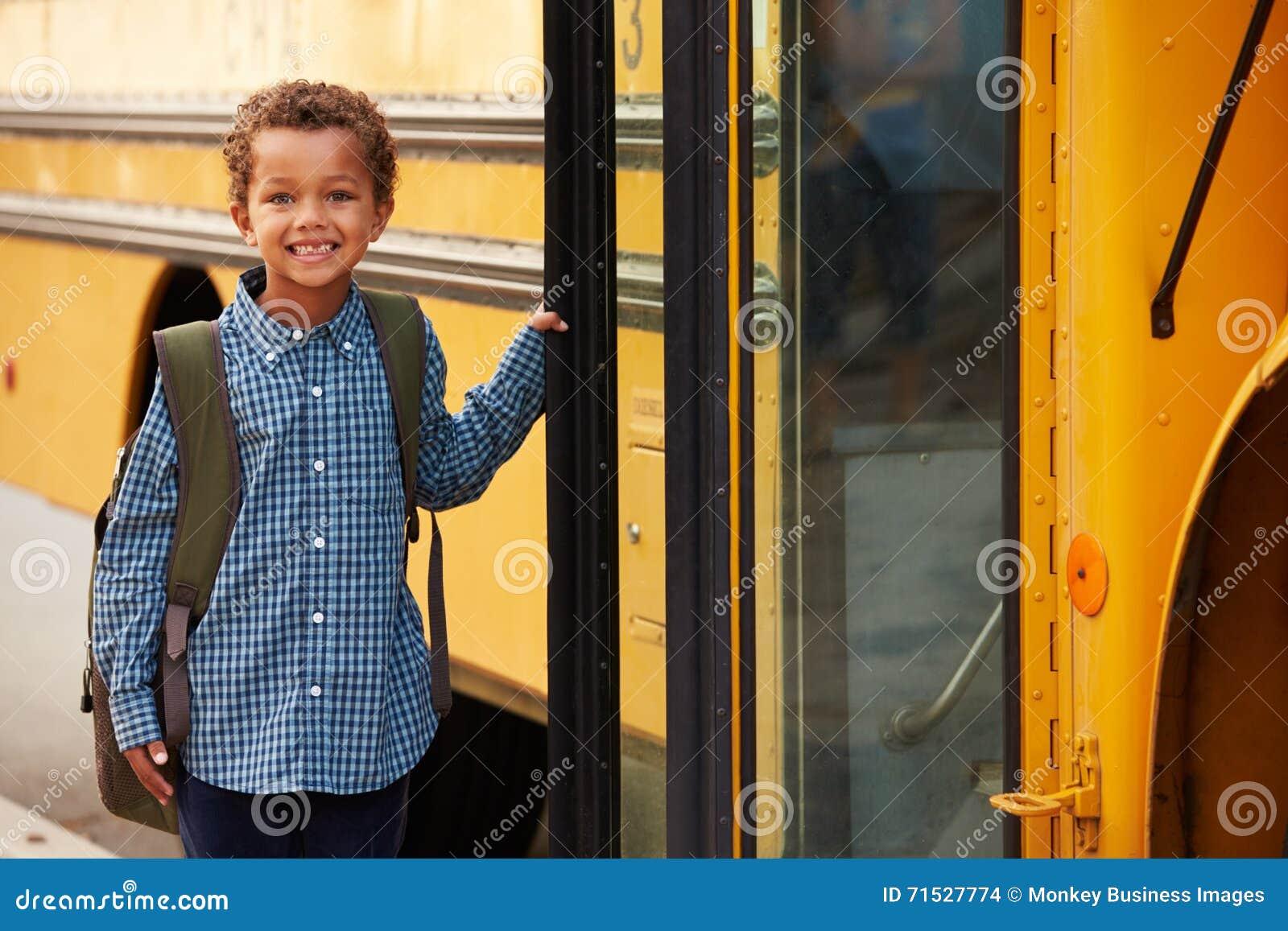 Grundskolapojke som får på en gul skolbuss