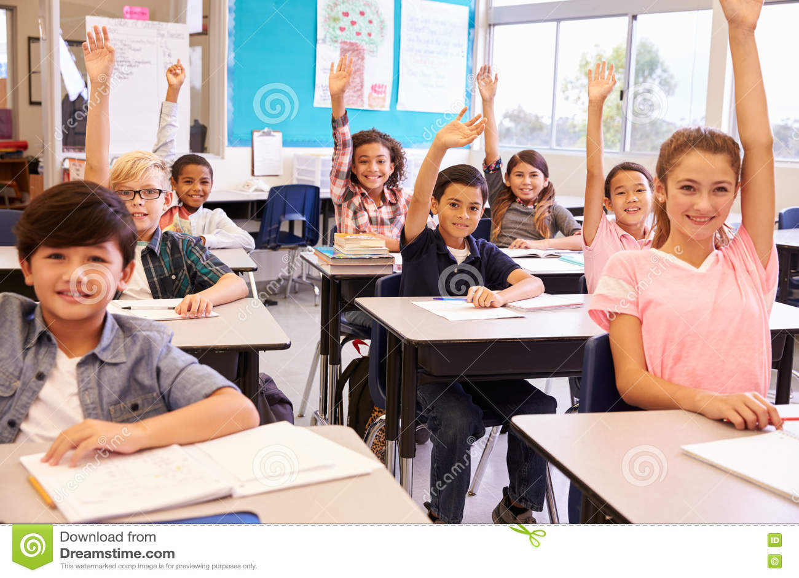 Grundskolaungar i ett klassrum som lyfter deras händer