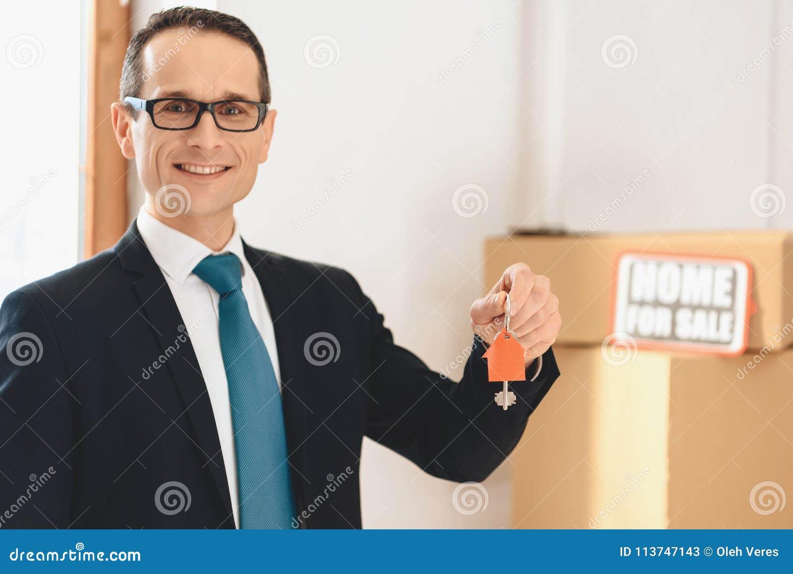 Grundstücksmakler, der Schlüssel mit Hausikone in der neuen Wohnung mit Pappschachteln hält