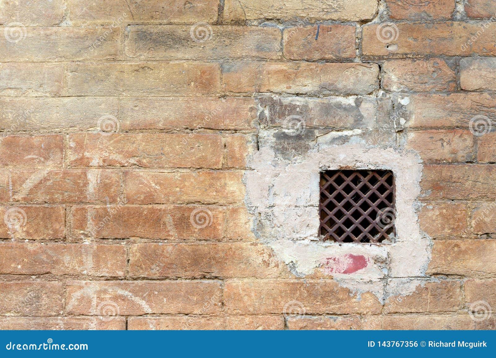 Grunge ściana z okno z rdzewiejącą żelazo kratownicą
