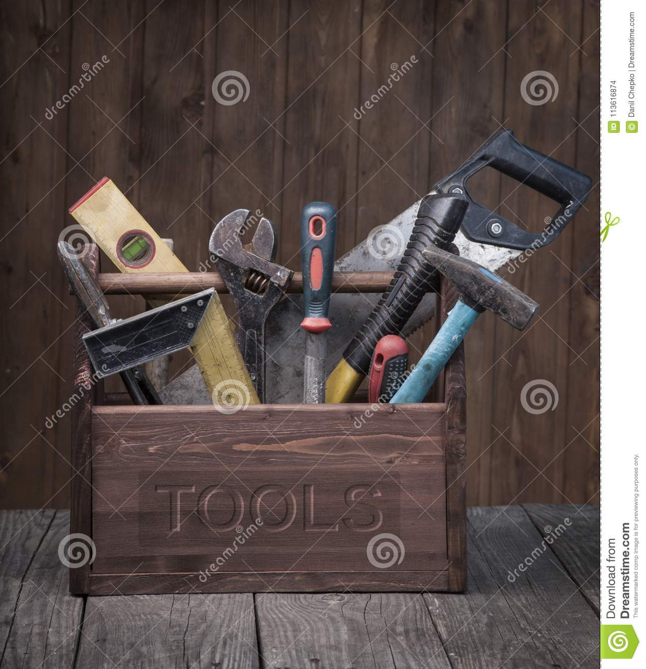 Grungy old tools on a wooden background front view.