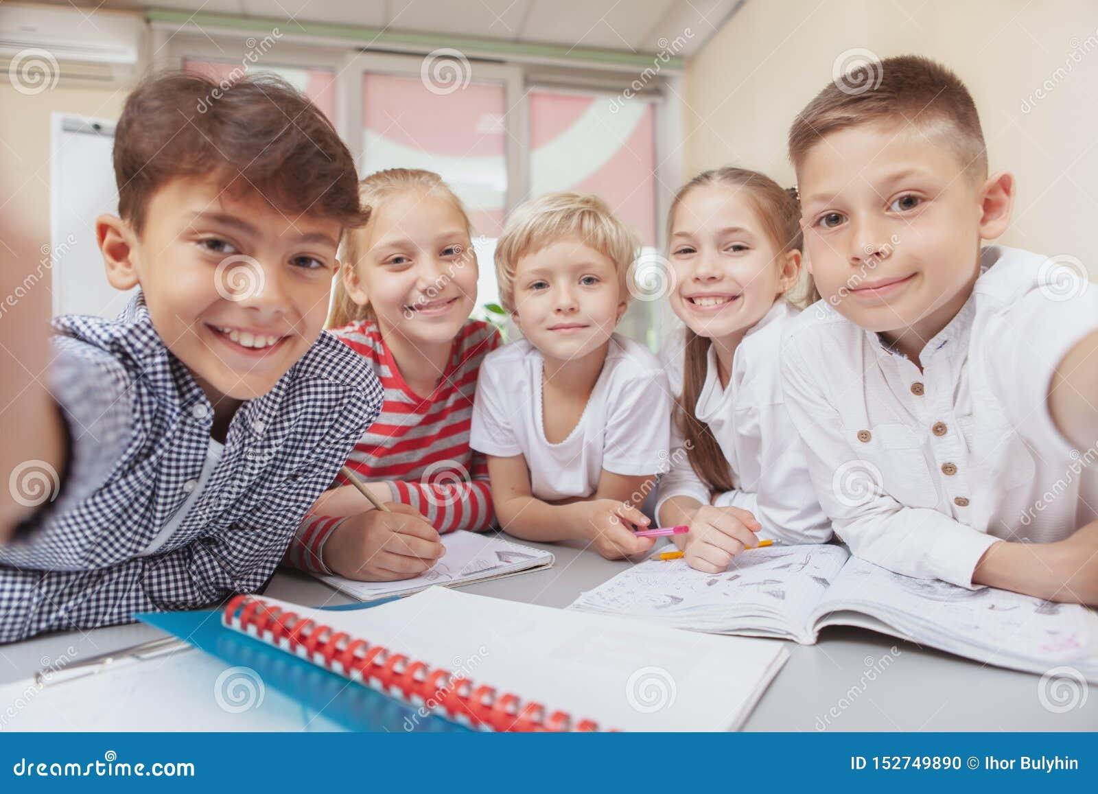 Grupa śliczni małe dzieci rysunkowi w sztuki klasie wpólnie