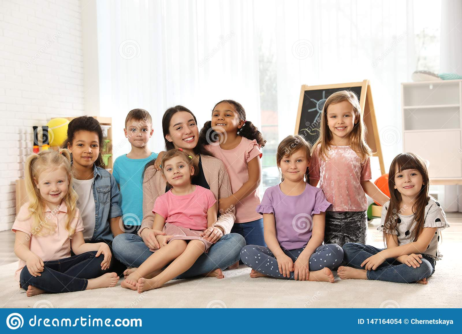 Grupa śliczni małe dzieci z nauczyciela obsiadaniem na podłodze