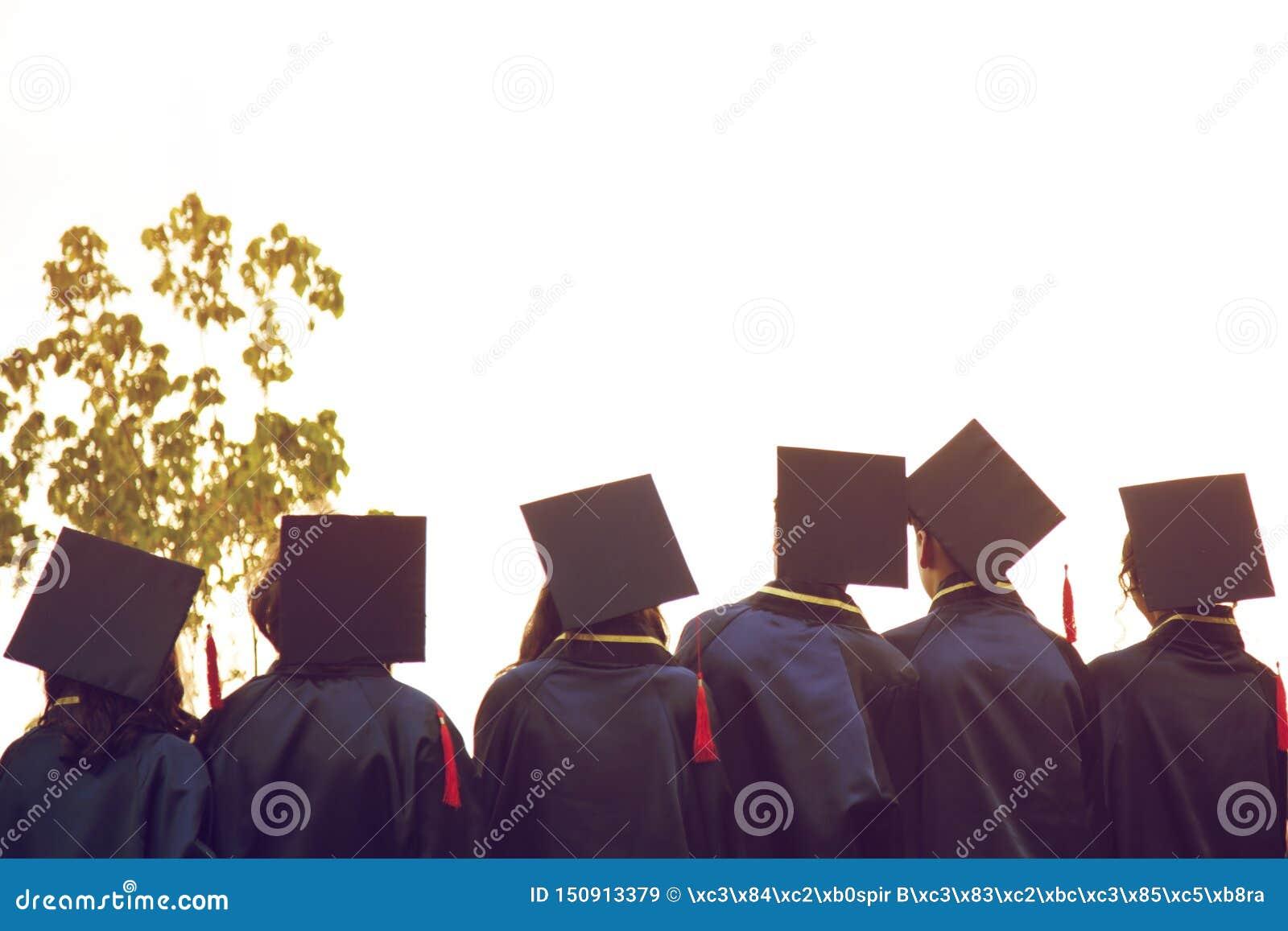 Grupa absolwenci podczas pocz?tku Poj?cie edukacji gratulacje w uniwersytecie Skalowanie ceremonia