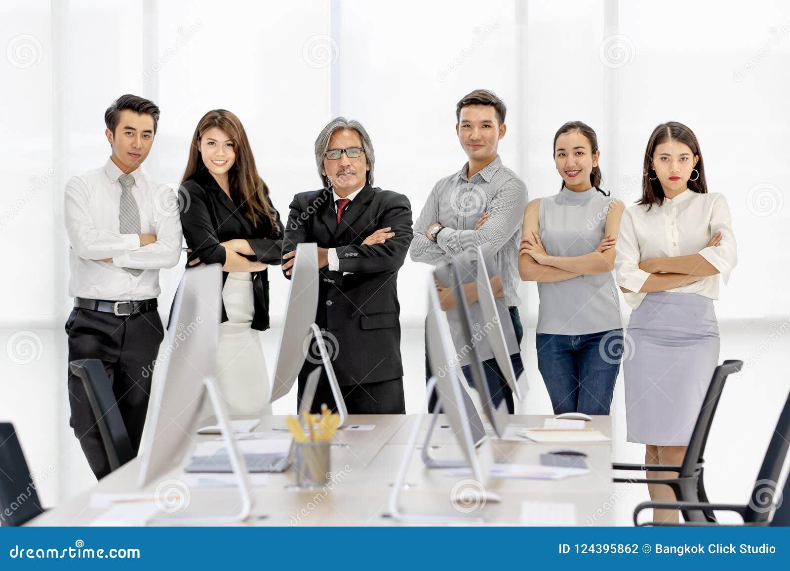 Grupa 6 Asaina ludzi biznesu stoi wpólnie w nowożytnym