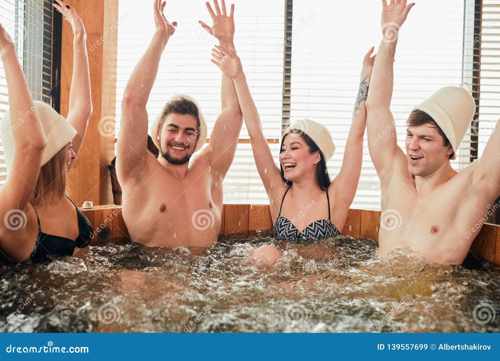 Grupa caucasian różnorodni przyjaciele cieszy się jacuzzi w hotelowym zdroju