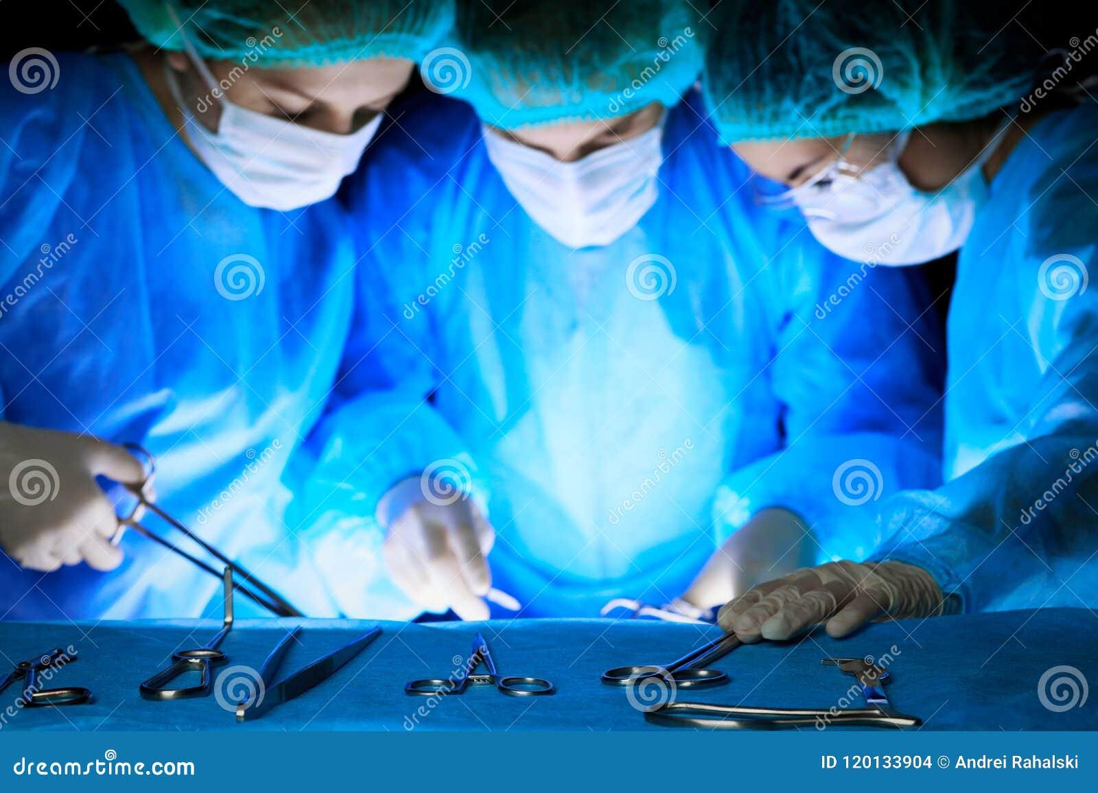 Grupa chirurdzy wykonuje operację w maskach Medycyna, operacja i przeciwawaryjni pomocy pojęcia,