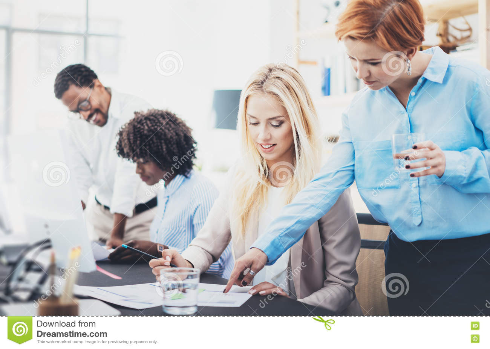 Grupa cztery coworkers dyskutuje plany biznesowych w biurze Młodzi ludzie robi doskonałym pomysłom Horyzontalny, zamazany tło,