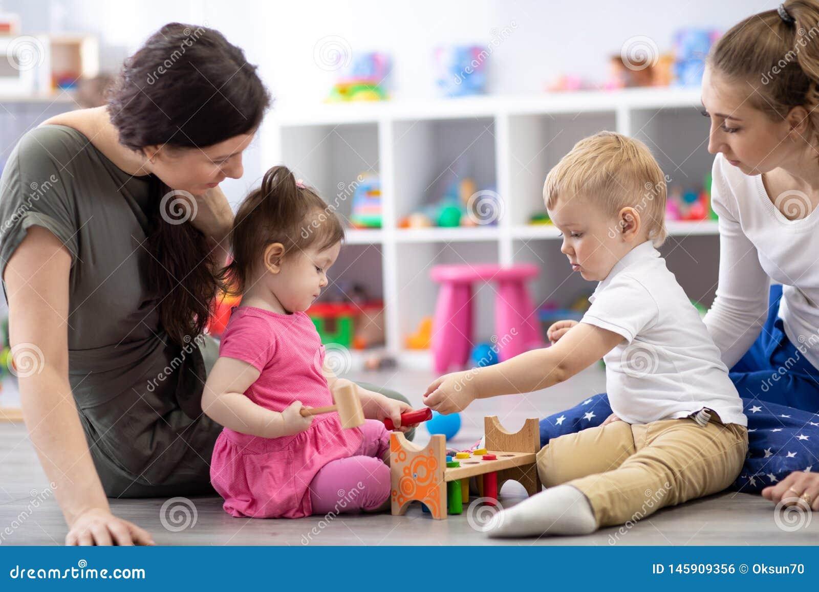 Grupa dzieci bawić się wraz z matkami w sali lekcyjnej w pepinierze lub preschool