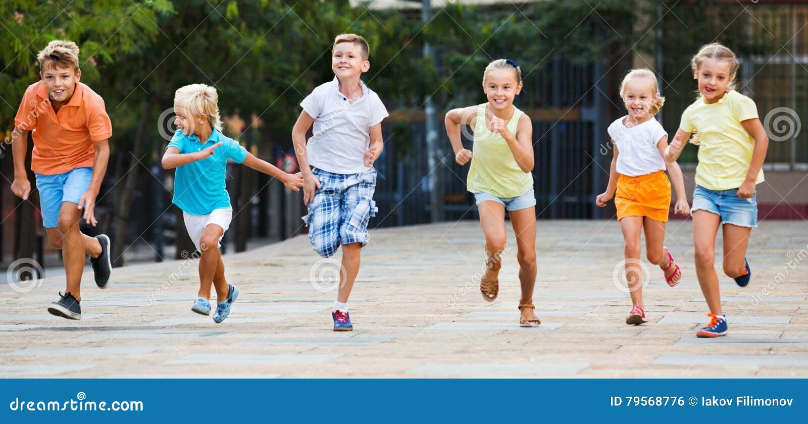 Grupa dzieci biega outdoors w miasto ulicie