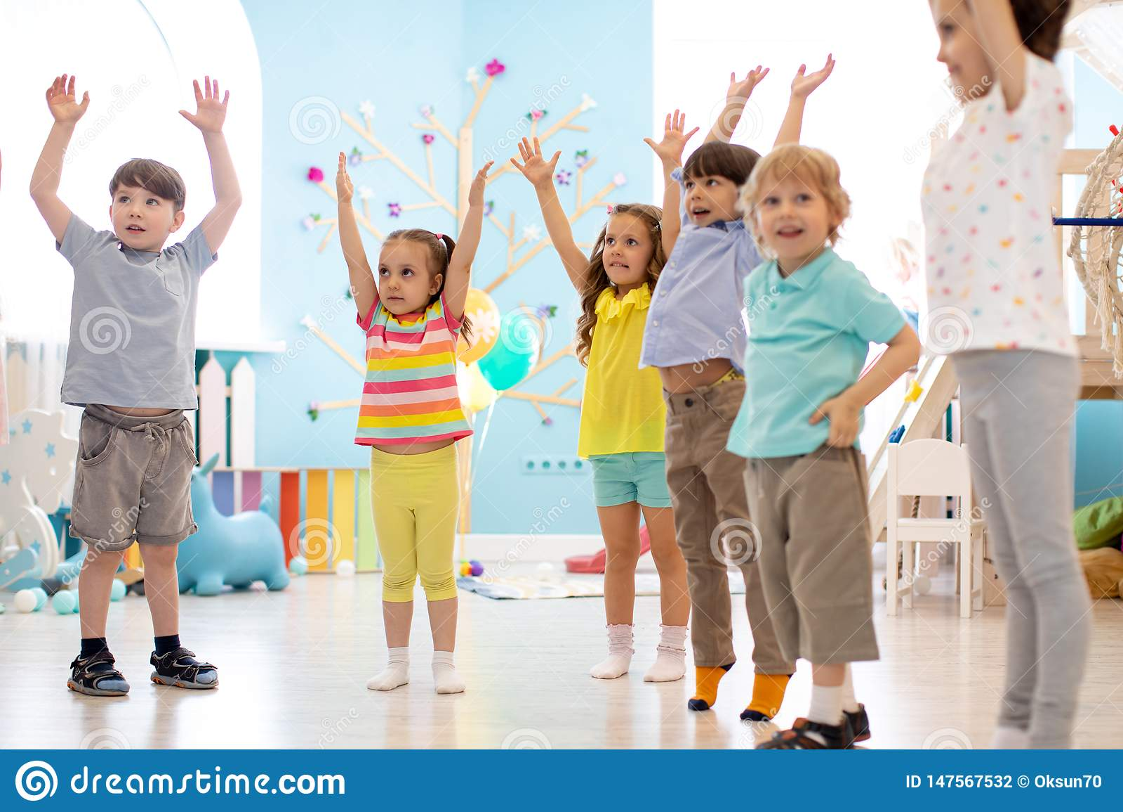 Grupa dzieci robi dzieciak gimnastyce w dziecinu
