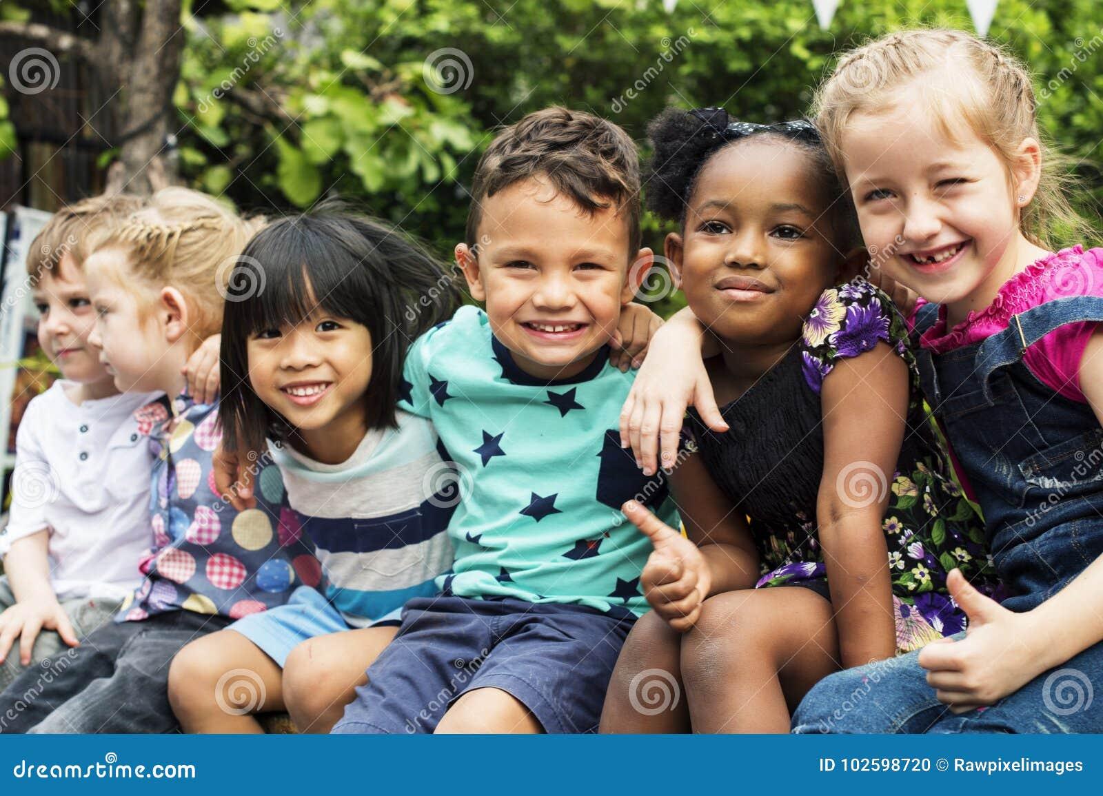 Grupa dzieciniec żartuje przyjaciel rękę wokoło obsiadania i uśmiechniętej zabawy